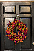 A black wooden door of a historic home decorated with a Popcorn Berry Christmas wreath on Tradd Street in Charleston, SC.