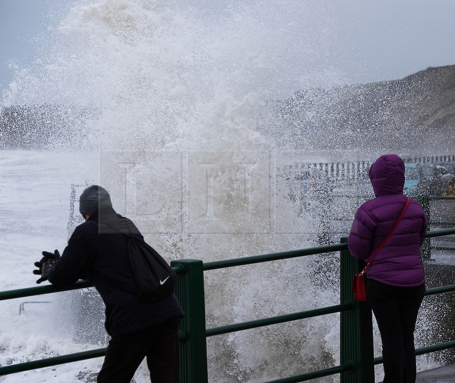 © Licensed to London News Pictures. <br /> 21/03/2015. <br /> <br /> Sandsend, North Yorkshire.<br /> <br /> Bystanders look on as huge waves crash against the sea wall at Sandsend in North Yorkshire. The exceptionally high Spring tides were created by the moon's 18-year cycle.<br /> <br /> Photo credit : Ian Forsyth/LNP