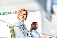 Young businesswoman working on computer with colleague in background at office