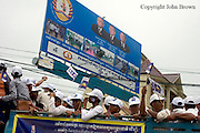 Men are waving pennants while riding in an old truck past a ruling party CPP sign depitying Cambodian PM Hun Sen (center) during a campaign rally for the opposing CNRP led by Sam Rainsy in Kampong Cham, Cambodia.