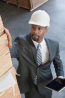 High angle view of African American male contractor inspecting wooden planks while holding tablet PC