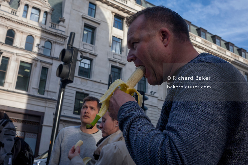 A family eat healthy, energy-giving bananas while visiting central London.