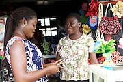 Esther Igwe serving a customer in her shop 'Goshen Decorates', where she makes and sells decorations for parties and events, Nigeria.<br /> <br /> Esther attended a business training workshop with Youth for Technology and also signed up to receive the business support texts.<br /> <br /> She has learnt a lot from the course and the text messages; including business planning, capital investment, diversifying incomes streams and improving customer relationship management. She says profit is up 40% as a result, that her confidence has improved.<br /> <br /> Esther started her business in 2010 because she had given birth to twins and with her previous three children the family were struggling financially.