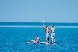 © Licenced to London News Pictures <br /> <br /> 24 June 2018 . Aberystwyth Wales UK<br /> <br /> UK Weather:  People paddle boarding on Sunday morning  on the flat calm waters of Cardigan Bay  in Aberystwyth on yet another bright and sunny day, as the UK heads into a mini heatwave, with temperatures forecast to hit 29º or 30º Celsius by the middle of the week<br /> <br /> photo credit Keith Morris/LNP