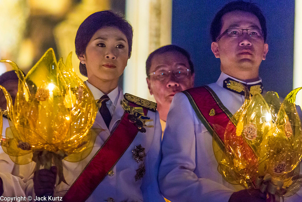 YINGLUCK SHINAWATRA (left), the Prime Minister of Thailand, and ANUSORN AMORNCHAT, her husband, (right) hold candles during the celebration of the birthday of the King in Bangkok. Thais observed the 86th birthday of Bhumibol Adulyadej, the King of Thailand, their revered King on Thursday. They held candlelight services throughout the country. The political protests that have gripped Bangkok were on hold for the day, although protestors did hold their own observances of the holiday. Thousands of people attended the government celebration of the day on Sanam Luang, the large public space next to the Grand Palace in Bangkok.