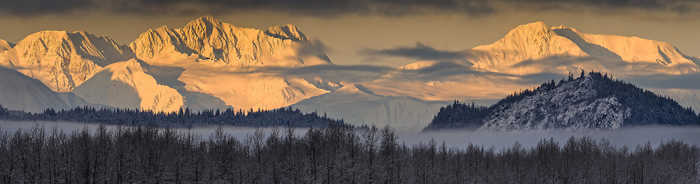 The Takhinsha Mountains near Haines, Alaska are bathed in the morning sunlight in this photo taken from the Alaska Chilkat Bald Eagle Preserve along the Chilkat River. Mountains in the Haines area are a popular destination for heli-skiing. SPECIAL NOTE: This image is a panorama composite consisting of multiple overlapping images stitched together.
