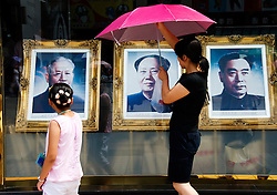 Portraits of former Chinese leaders in window of shop on Wangfujing shopping street in Beijing China
