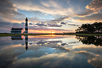 Heavy rains create shallow reflecting puddles in front of the historic Bodie Island Lighthouse at sunrise along Cape Hatteras National Seashore, North Carolina.