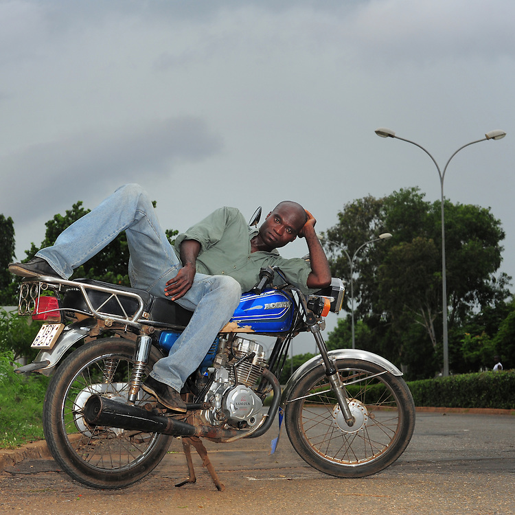 12-05-25   - LOME, TOGO -    Zemidjan ('take me quickly' in  Fon) driver Isodore Lokou demonstrates how he sleeps on his motorcycle in Lomé, Togo on May 25. Underpaid, rarely thanked and working all hours to make a meagre living, they find very few moments of calm and quiet in their lives. And so, the moto-taxi men have perfected various ways of calmly sleeping on their motorbike as they wait for  their next customer. And so, on the move amidst the chaos and bustle of daily life, they relax and sleep.  Photo by Daniel Hayduk