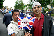 Two British Asians in Jubilee Street in Stepney Green, east London at a street party to celebrate Queen Elizabeth II's Golden Jubilee. Celebrations took place across the United Kingdom with the centrepiece a parade and fireworks at Buckingham Palace, the Queen's London residency. Queen Elizabeth ascended to the British throne in 1952 upon the death of her father, King George VI.