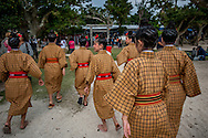 Young performers run toward the Yomochi-utaki's stage at the Tanadui Matsuri (Festival), which has a 600 year history on the small coral island of Taketomi.  Tanadui Matsuri has been designated by the Japanese government as an important intangible cultural heritage.  The festival is held in part to ensure a good harvest.  Taketomi Island, Okinawa Prefecture, Japan.
