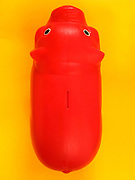 a red plastic piggy bank seen from above