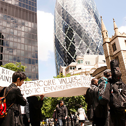 London, UK - 15 June 2012: protesters holding a white coffin pass by the Gherkin during the Carnival of Dirt. More than 30 activist groups from London and around the world have come together to highlight the illicit deeds of mining and extraction companies.