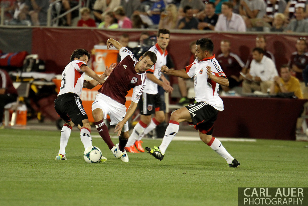 July 7th, 2013 - Colorado Rapids midfielder Nathan Sturgis (24) attempts to bring the ball between D.C. United midfielder John Thorrington (8) and forward Carlos Ruiz (20) in the second half of action in the Major League Soccer match between D.C. United and the Colorado Rapids at Dick's Sporting Goods Park in Commerce City, CO