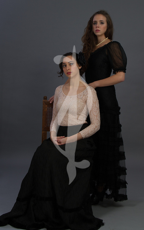Female models posing together in Victorian clothes.