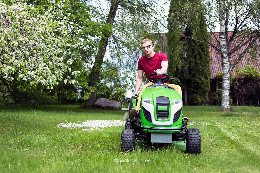 Young man, gardener driving ride on mower. Mowing grass in yard, tractor. Gardening in Estonia.