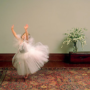 Little ballerina, Halley, dancing on an oriental rug in her white tutu with her arms stretched upward. White bouquet of flowers in a vase sit on a small, wood trunk behind her.