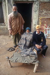 Group of men outside house; with elderly man sitting in bed with blanket wrapped around him,