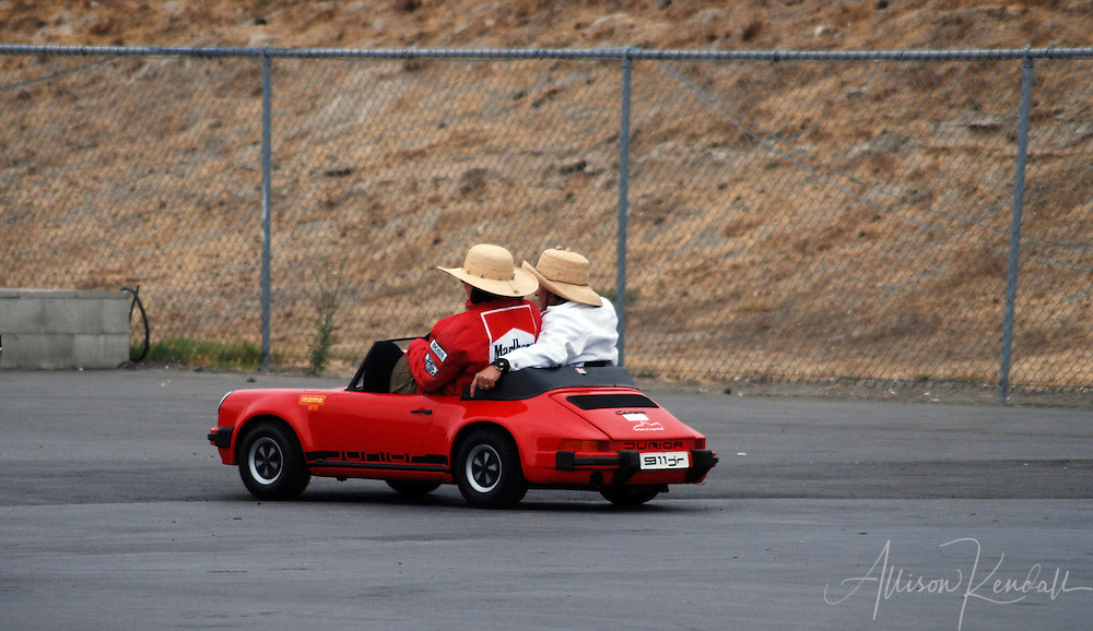 Two vintage racing enthusiasts enjoy a last spin around the paddock at Laguna Seca in a miniature Porsche