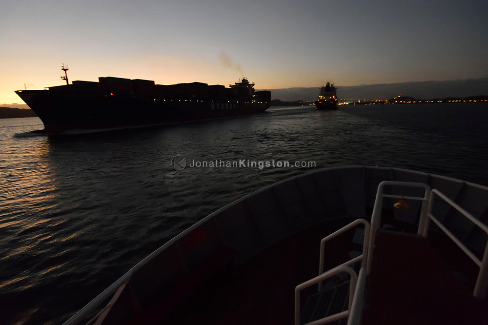 Large container ships pass each other at sunset in the entrance to the Panama Canal, near Panama city, Panama.