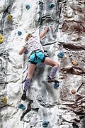 Young teen girl climbs up an artificial climbing wall