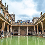 A water-level view of the Roman baths in Bath, Somerset. The original location was used during the Roman Empire. In centuries since, the building has been constructed around them, but the source of the warm natural springs remains.