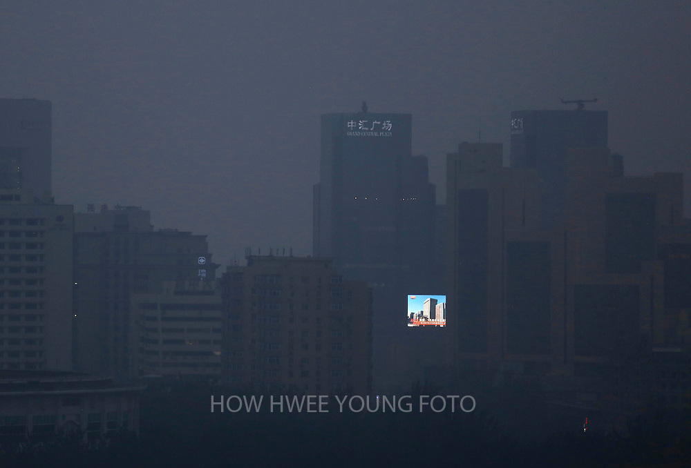 epaselect epa04416427 A large LCD screen showing a view of blue skies and buildings is seen amidst the smog clad city of Beijing, China, 25 September 2014. Vows to tackle climate change, commitments to meet emission reduction targets and promises of financial assistance were thick on the ground on 23 September when world leaders were meeting for the UN Climate Summit. China's Vice  Premier Zhang Gaoli pledged that China will provide financial help to developing countries to tackle climate change and will give 6 million dollars to a fund set up by Ban to assist developing nations.  EPA/HOW HWEE YOUNG