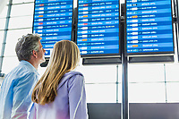 Rear view of mature man with his daughter looking at their flight on monitor in airport
