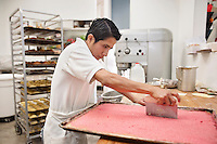 Young male baker cutting pastry on tray in bakery