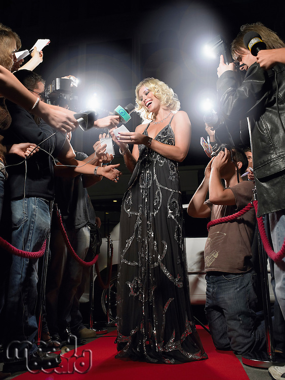 Woman signing autographs on red carpet