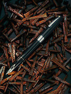 still life of Sheaffer fountain pen on a bed of rusty cut nails.