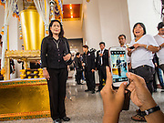 19 OCTOBER 2014 - BANG BUA THONG, NONTHABURI, THAILAND: A mourner has her picture taken with a smart phone at Apiwan Wiriyachai's cremation at Wat Bang Phai in Bang Bua Thong, a Bangkok suburb, Sunday. Apiwan was a prominent Red Shirt leader. He was member of the Pheu Thai Party of former Prime Minister Yingluck Shinawatra, and a member of the Thai parliament and served as Yingluck's Deputy Prime Minister. The military government that deposed the elected government in May, 2014, charged Apiwan with Lese Majeste for allegedly insulting the Thai Monarchy. Rather than face the charges, Apiwan fled Thailand to the Philippines. He died of a lung infection in the Philippines on Oct. 6. The military government gave his family permission to bring him back to Thailand for the funeral. His cremation was the largest Red Shirt gathering since the coup.     PHOTO BY JACK KURTZ