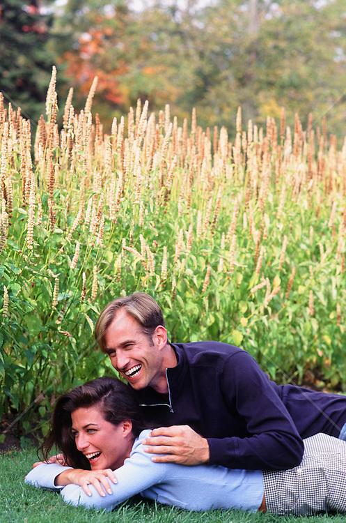 romantic couple together outdoors on grass in a garden