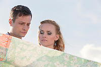 Couple reading map against sky