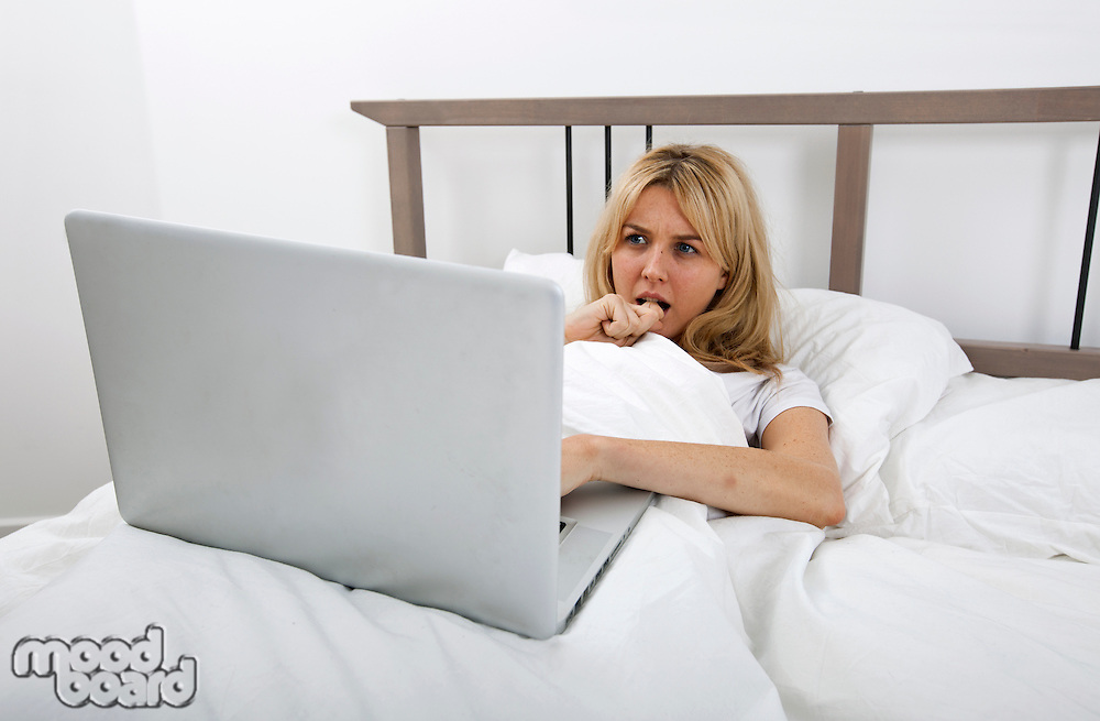 Thoughtful young woman looking at laptop in bed