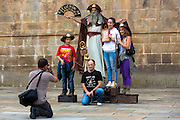 Tourists pose with pilgrim mime artist by Cathedral in Santiago de Compostela, Galicia, Spain