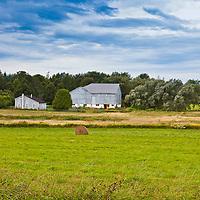 A large barn, viewed across an autumn field, under a heavy sky.