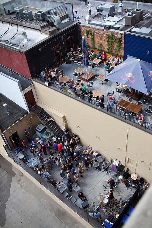 The Wigg Report plays behind Slim's while patrons at The Hive enjoy themselves and two dudes fix a rooftop air conditioner, Hopscotch Music Festival, Friday, Sept. 8, 2011.
