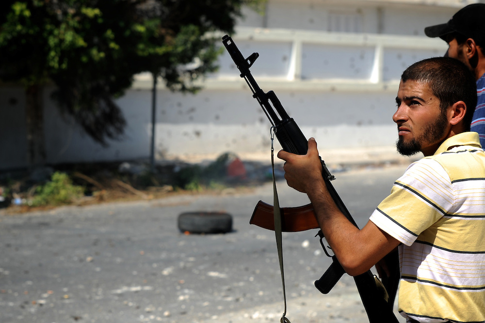A rebel fighter await orders to attack Zawiyah's the central square, a strategically position controlled by pro-Gaddafi troops.
