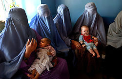 KABUL,AFGHANISTAN - AUGUST 29: Afghan women wait with their children to be seen by a doctor in the Indira Ghandi Hospital for Children August 29, 2002 in Kabul Afghanistan. The hospital has 300 beds but usually it is filled at double capacity with only 118 doctors. (Photo by Ami Vitale/Getty Images)