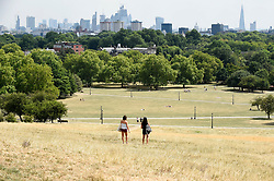 © Licensed to London News Pictures. 25/07/2018. LONDON, UK.  People enjoy the weather on Primrose Hill amidst parched grass and hot conditions.  The forecast is for temperatures to rise to 35C by the end of the week.  Photo credit: Stephen Chung/LNP