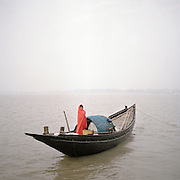 A fisherman in the icy winter breeze gets ready to go out fishing in the Sunderbans.