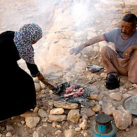 Doha and her father cook small pieces of meat on the fire