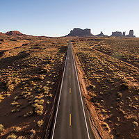 USA, Utah, Monument Valley Navajo Tribal Park, Aerial view of desert highway through towering sandstone mesas at sunrise