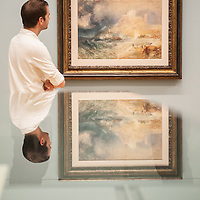 London, UK - 8 September 2014: a gallery assistant poses next to 'Bamborough Castle c.1837' by J.M.W. Turner.