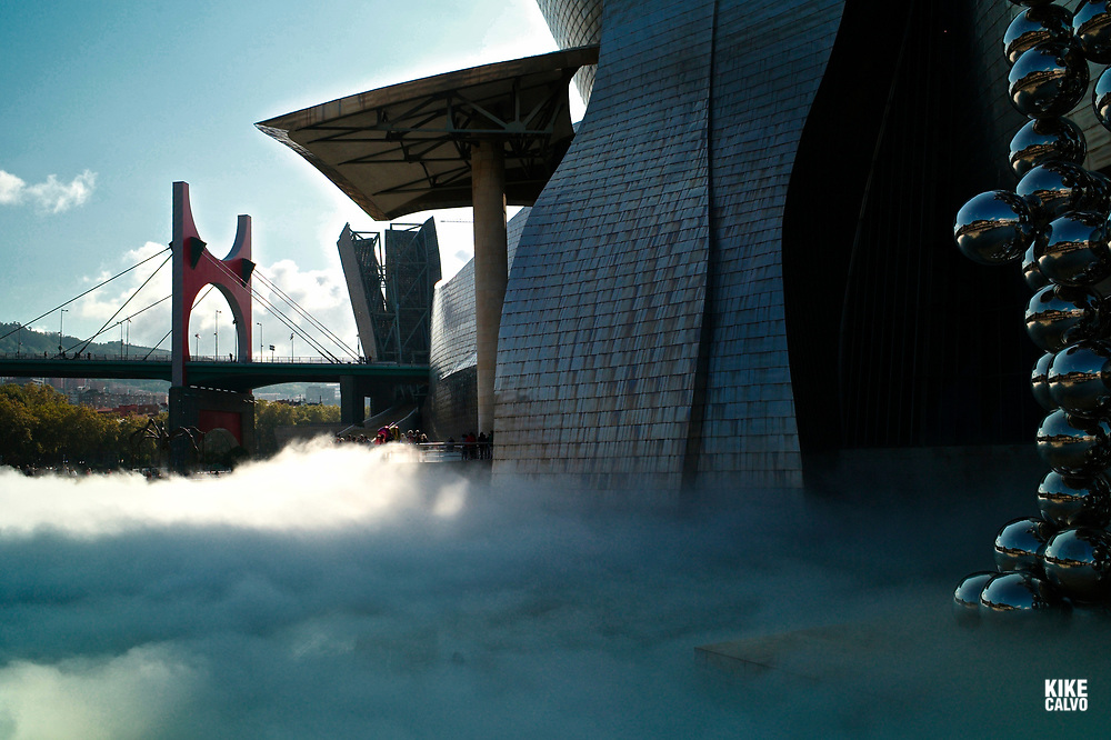 The Sculpture Tall Tree & The Eye by Anish Kapoor, surrounded by The Fog sculpture designed as a sculptural medium by Fujiko Nakaya, The Guggenheim Museum in Bilbao with La Salve Bridge on the background