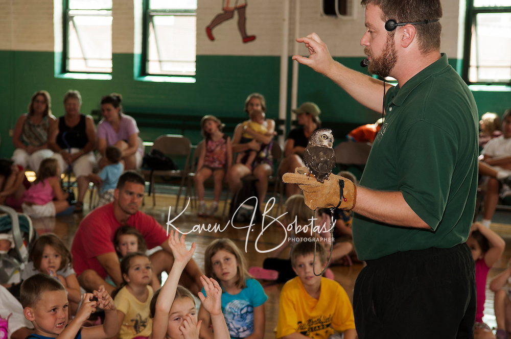Jeremy Phillips of the Squam Lakes Science Center presents a saw-whet owl to the children gathered for Laconia Library's Summer Reading program event at the Laconia Community Center Wednesday afternoon.  (Karen Bobotas/for the Laconia Daily Sun)