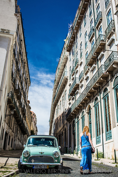 A girl with a dress the colour of the sky walks past a blue Mini Rover car in the old city of Lisbon. Blue (Azul) is a defining colour in Portoguese culture, its english meaning keep a link with portoguese saudade.