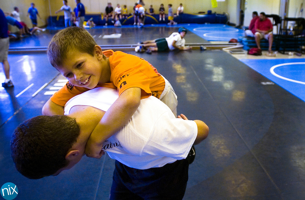 Camper Ryan Saubir, 10, climbs on Mount Pleasant High School wrestler Chris Bowman during the Mount Pleasant Youth Wrestling Camp at the school Monday morning. The camps runs through Thursdy and teaches fundemental wrestling skills.
