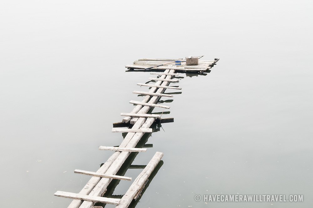 A narrow wooden jetty on the calm waaters of West Lake (Ho Tay) in Hanoi, Vietnam.
